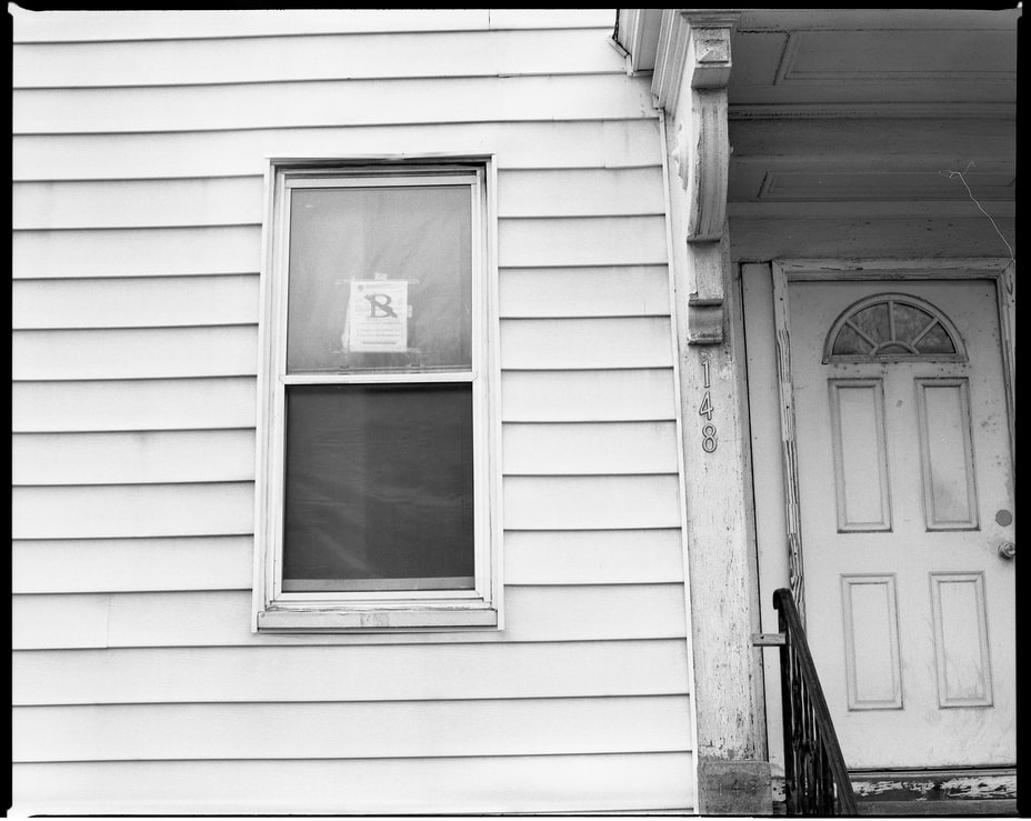 Black and white image of a house's front door and window